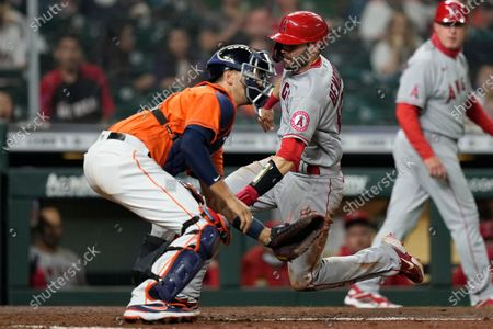 Los Angeles Angels' Anthony Bemboom, center, scores as Houston Astros catcher Jason Castro reaches for the throw during the 10th inning of a baseball game, in Houston