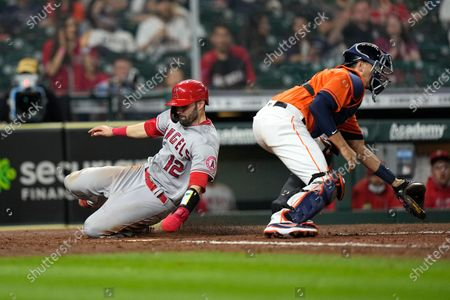 Los Angeles Angels' Anthony Bemboom (12) scores as Houston Astros catcher Jason Castro reaches for the throw during the 10th inning of a baseball game, in Houston