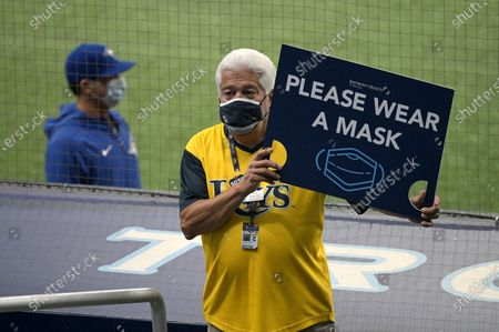 An usher holds a sign asking spectators to wear face masks to help curb the spread of COVID-19 during the third inning of a baseball game between the Tampa Bay Rays and the Toronto Blue Jays, in St. Petersburg, Fla