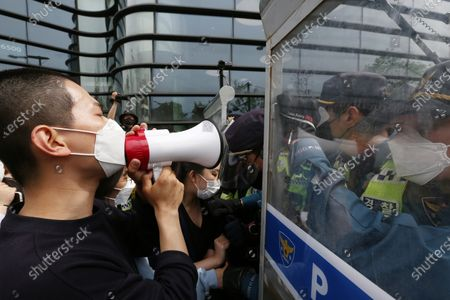 Stock Photo of University student protesters (L) try to go Japanese embassy as Police officials block in a protest against Japan's decision to release radioactive water from the Fukushima Nuclear Power Plant into the ocean, outside the Japanese embassy in Seoul, South Korea, 24 April 2021. On 13 April, the Japanese government decided to discharge radioactive water from the crippled Fukushima nuclear plant into the Pacific Ocean.
