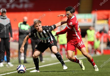 Newcastle's Matt Ritchie, left, challenges for the ball with Liverpool's Trent Alexander-Arnold during the English Premier League soccer match between Liverpool and Newcastle United at Anfield stadium in Liverpool, England