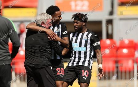 Newcastle's Joe Willock, center, celebrates with his coach Steve Bruce, left, and his teammate Allan Saint-Maximin after scoring his side's opening goal during the English Premier League soccer match between Liverpool and Newcastle United at Anfield stadium in Liverpool, England