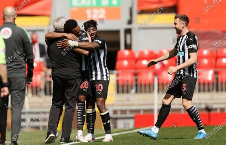 Newcastle's Joe Willock, third from right, celebrates with his coach Steve Bruce, left, his teammates Paul Dummett, right, and Allan Saint-Maximin after scoring his side's opening goal during the English Premier League soccer match between Liverpool and Newcastle United at Anfield stadium in Liverpool, England