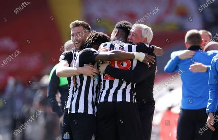 Newcastle's Joe Willock, second from right, celebrates with his coach Steve Bruce, right, and his teammates after scoring his side's opening goal during the English Premier League soccer match between Liverpool and Newcastle United at Anfield stadium in Liverpool, England