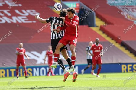 Newcastle's Joelinton, left, jumps for the ball with Liverpool's Trent Alexander-Arnold during the English Premier League soccer match between Liverpool and Newcastle United at Anfield stadium in Liverpool, England