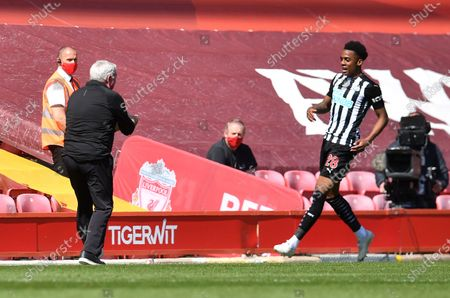 Newcastle's Joe Willock, right, celebrates with his head coach Steve Bruce after scoring his side's opening goal during the English Premier League soccer match between Liverpool and Newcastle United at Anfield stadium in Liverpool, England