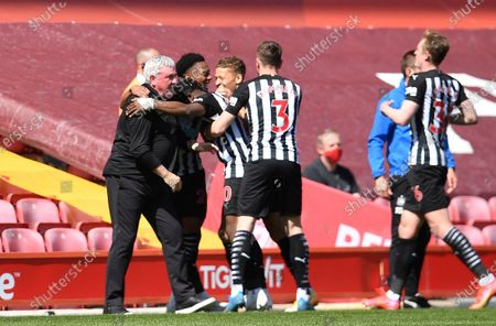 Newcastle's Joe Willock, second from right, celebrates with his head coach Steve Bruce, left, and his teammates after scoring his side's opening goal during the English Premier League soccer match between Liverpool and Newcastle United at Anfield stadium in Liverpool, England