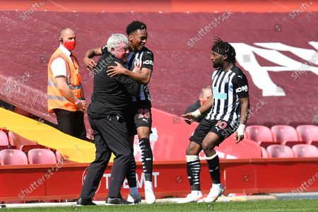 Newcastle's Joe Willock, center, celebrates with his head coach Steve Bruce, left, and his teammate Allan Saint-Maximin after scoring his side's opening goal during the English Premier League soccer match between Liverpool and Newcastle United at Anfield stadium in Liverpool, England