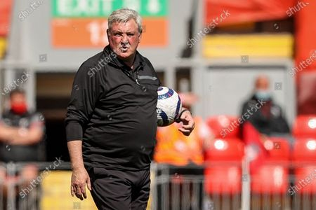 Newcastle manager Steve Bruce holds a ball during the English Premier League soccer match between Liverpool FC and Newcastle United in Liverpool, Britain, 24 April 2021.