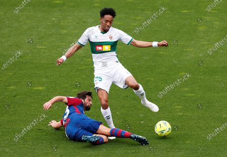 Stock Image of Levante's UD defender Coke Andujar (L) vies for the ball with Elche's Colombian midfielder Johan Mojica (R) during the Spanish LaLiga match held between Elche CF and LEvante UD at Martinez Valero stadium in Elche, Spain, 24 April 2021.
