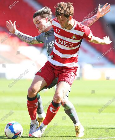 Doncaster defender Joe Wright (5) holds off Barrie McKay of Fleetwood Town (19)  during the EFL Sky Bet League 1 match between Doncaster Rovers and Fleetwood Town at the Keepmoat Stadium, Doncaster
