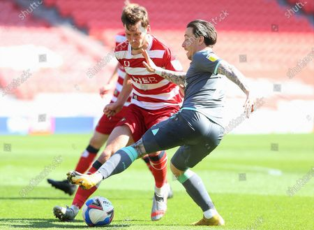 Barrie McKay of Fleetwood Town (19)  takes on Doncaster defender Joe Wright (5) during the EFL Sky Bet League 1 match between Doncaster Rovers and Fleetwood Town at the Keepmoat Stadium, Doncaster