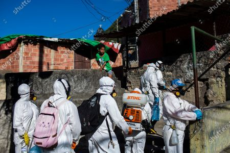 Stock Photo of Volunteers spray disinfectant to help contain the spread of the new coronavirus, in the Santa Marta slum of Rio de Janeiro, Brazil
