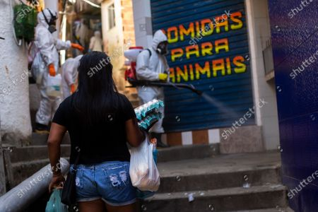 Resident with an armful of groceries pauses as volunteers spray disinfectant in an alley to help contain the spread of the new coronavirus, in the Santa Marta slum of Rio de Janeiro, Brazil