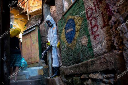 Thiago Firmino sprays disinfectant in an alley to help contain the spread of the new coronavirus, in the Santa Marta slum of Rio de Janeiro, Brazil