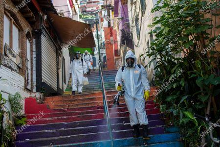 Stock Image of Thiago Firmino, right, sprays disinfectant to help contain the spread of the new coronavirus, in the Santa Marta slum of Rio de Janeiro, Brazil