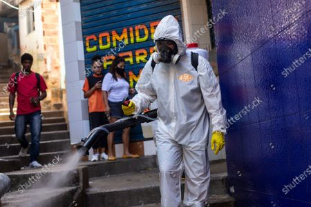 Volunteer sprays disinfectant in an alley to help contain the spread of the new coronavirus, in the Santa Marta slum of Rio de Janeiro, Brazil