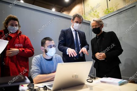French Minister for Solidarity and Health Olivier Veran and French Labor Minister Elisabeth Borne speaks to medical staff during their visit of the vaccination center in Sainte-Genevieve-des-Bois