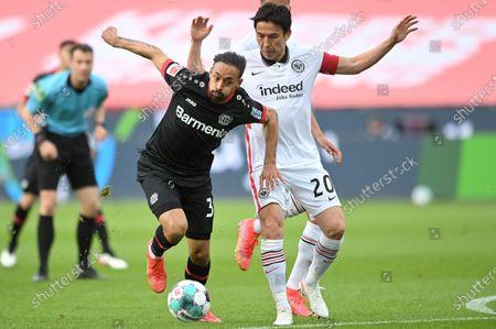 Frankfurt's Makoto Hasebe (R) in action against Leverkusen's Karim Bellarabi (L) during the German Bundesliga soccer match between Bayer 04 Leverkusen and Eintracht Frankfurt in Leverkusen, Germany, 24 April 2021.