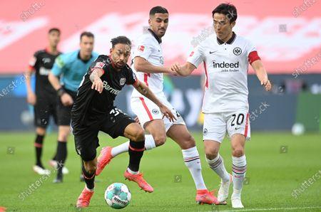 Leverkusen's Karim Bellarabi (L) in action against Frankfurt players Makoto Hasebe (R) and Aymen Barkok (C) during the German Bundesliga soccer match between Bayer 04 Leverkusen and Eintracht Frankfurt in Leverkusen, Germany, 24 April 2021.