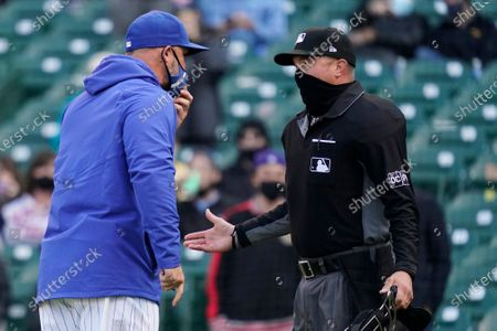 Chicago Cubs manager David Ross, left, argues with umpire Cory Blaser during the ninth inning of a baseball game against the Milwaukee Brewers in Chicago