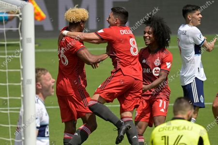 Toronto FC defender Luke Singh (26) is congratulated by midfielder Marco Delgado (8) and forward Jayden Nelson (11) after Singh scored a goal during the first half of an MLS soccer match against the Vancouver Whitecaps, in Orlando, Fla