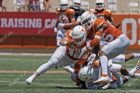 Texas defenders Jake Ehlinger, left, and B.J. Foster, right, tackle Kayvontay Dixon (16) during the first half of the Texas Orange and White Spring Scrimmage football game in Austin, Texas
