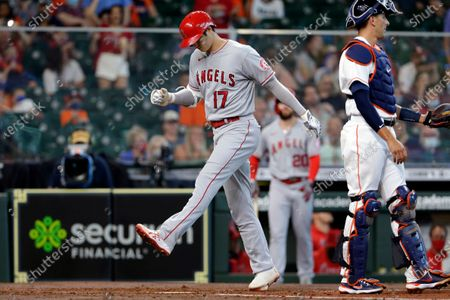 Los Angeles Angels designated hitter Shohei Ohtani (17) crosses the plate on his home run next to Houston Astros catcher Jason Castro, right, during the third inning of a baseball game, in Houston