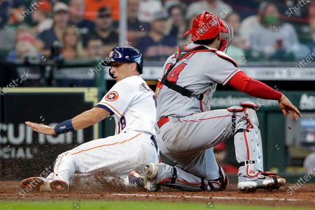 Houston Astros' Jason Castro (18) scores as Los Angeles Angels catcher Kurt Suzuki (24) missed the throw during the fourth inning of a baseball game, in Houston