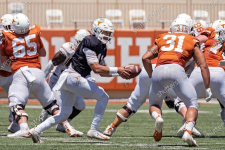 Texas quarterback Casey Thompson looks to hand-off to Texas running back Gabriel Watson (31) during the first half of the Texas Orange and White Spring Scrimmage football game in Austin, Texas