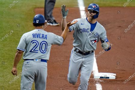 Stock Picture of Toronto Blue Jays' Randal Grichuk, right, high fives third base coach Luis Rivera after Grichuk hit a three run home run off Tampa Bay Rays' Brent Honeywell Jr. during the first inning of a baseball game, in St. Petersburg, Fla