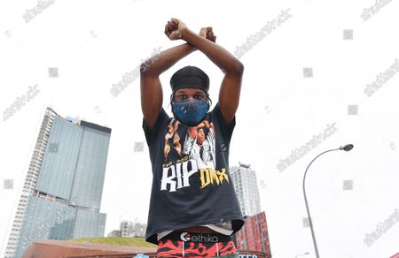 A fan makes an X with his arms in honor of the late hip hop artist DMX in front of Barclays Center in Brooklyn, New York City, where a memorial was held.