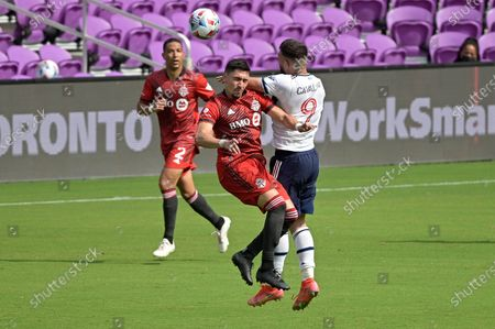 Toronto FC midfielder Marco Delgado, center, and Vancouver Whitecaps forward Lucas Cavallini (9) compete for a header during the second half of an MLS soccer match, in Orlando, Fla