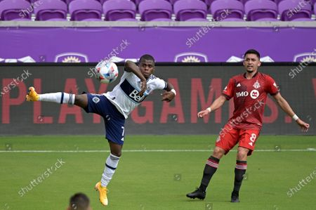 Stock Picture of Vancouver Whitecaps forward Deiber Caicedo (7) and Toronto FC midfielder Marco Delgado (8) compete for a ball during the first half of an MLS soccer match, in Orlando, Fla
