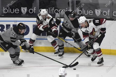 Los Angeles Kings center Jaret Anderson-Dolan (28), Arizona Coyotes defenseman Alex Goligoski (33), Kings right wing Carl Grundstrom (91) and Coyotes center John Hayden (15) reach for the puck during the third period of an NHL hockey game, in Los Angeles. Arizona won 4-0