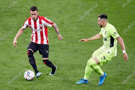 Stock Photo of Alex Berenguer of Athletic Club competes for the ball with Hector Miguel Herrera of Atletico de Madrid during the La Liga match between Athletic Club and Club Atletico de Madrid at San Mames stadium on April 25, 2021 in Bilbao, Spain.