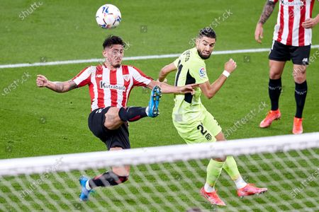 Unai Vencedor of Athletic Club duels for the ball with Yannick Carrasco of Atletico de Madrid during the La Liga match between Athletic Club and Club Atletico de Madrid at San Mames stadium on April 25, 2021 in Bilbao, Spain.