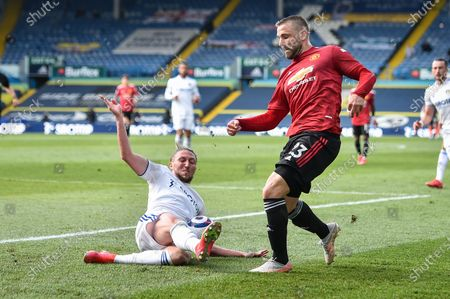 Luke Ayling (L) of Leeds tackles Luke Shaw (R) of Manchester United during the English Premier League soccer match between Leeds United and Manchester United in Leeds, Britain, 25 April 2021.