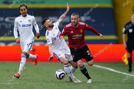 Stuart Dallas (C) of Leeds in action against Luke Shaw (R) of Manchester United during the English Premier League soccer match between Leeds United and Manchester United in Leeds, Britain, 25 April 2021.