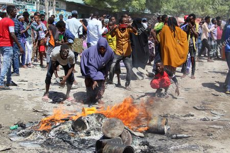 Stock Image of Somalis add fuel to burning barricades during a protest against the Somali president in the streets of Fagah cross in northern Mogadishu, Somalia, 25 April 2021. Gunfire rang out in the northern part of Somlia's capital Mogadishu Sunday as forces loyal to commander Saney Abdulle a break away military faction engaged Somali government soldiers. There has been growing opposition to Somalia's term extension by Somali lawmakers in Federal government. The African Union has also voiced its concern over Somalia's lower house of parliament voting to extend the mandate of President Mohamed Abdullahi Farmaajo.