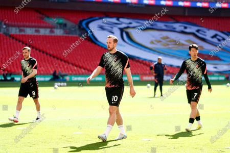 Tottenham's Harry Winks, Harry Kane and Son Heung-min, from left to right, walk on the pitch during warmup before the English League Cup final soccer match between Manchester City and Tottenham Hotspur at Wembley stadium in London
