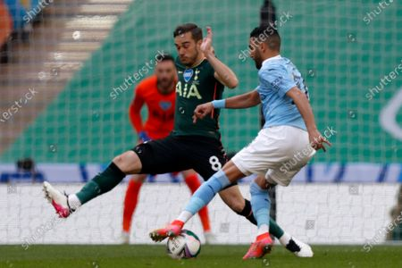 Tottenham's Harry Winks tries to block Manchester City's Riyad Mahrez, right, during the English League Cup final soccer match between Manchester City and Tottenham Hotspur at Wembley stadium in London