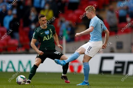 Manchester City's Kevin De Bruyne shoots the ball past Tottenham's Giovani Lo Celso, left, during the English League Cup final soccer match between Manchester City and Tottenham Hotspur at Wembley stadium in London