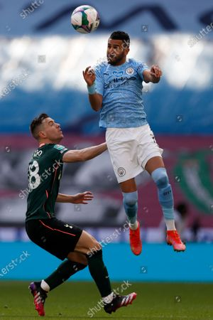Manchester City's Riyad Mahrez heads the ball above Tottenham's Giovani Lo Celso, left, during the English League Cup final soccer match between Manchester City and Tottenham Hotspur at Wembley stadium in London