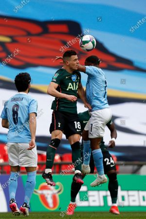 Manchester City's Raheem Sterling, right, jumps for the ball with Tottenham's Giovani Lo Celso during the English League Cup final soccer match between Manchester City and Tottenham Hotspur at Wembley stadium in London