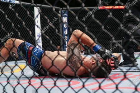 Chris Weidman on the canvas with a broken leg ending his UFC 261 mixed martial arts fight, in Jacksonville, Fla. This is the first UFC event since the onset of the COVID-19 pandemic to feature a full crowd in attendance