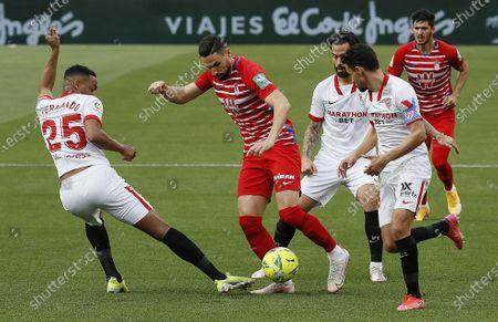 Sevilla's Fernando Reges (L) in action against Granada's Antonio Puertas (C) during the Spanish La Liga soccer match between Sevilla FC and Granada CF at Ramon Sanchez Pizjuan stadium in Seville, Spain, 25 April 2021.