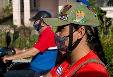Woman wearing a cap with an image of Fidel Castro and Hugo Chavez take part in a rally in protest of the US Embargo against Cuba in Santa Clara, Cuba