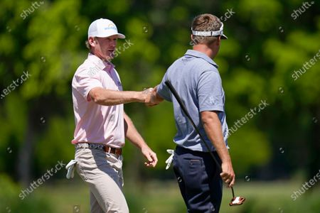 Brandt Snedeker, left, reacts with teammate Keith Mitchell after making his putt on the 11th green during the final round of the PGA Zurich Classic golf tournament at TPC Louisiana in Avondale, La