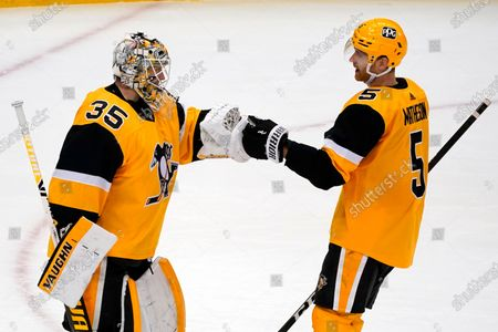 Pittsburgh Penguins goaltender Tristan Jarry (35) celebrates with defenseman Mike Matheson after shutting out the Boston Bruins 1-0 in an NHL hockey game in Pittsburgh
